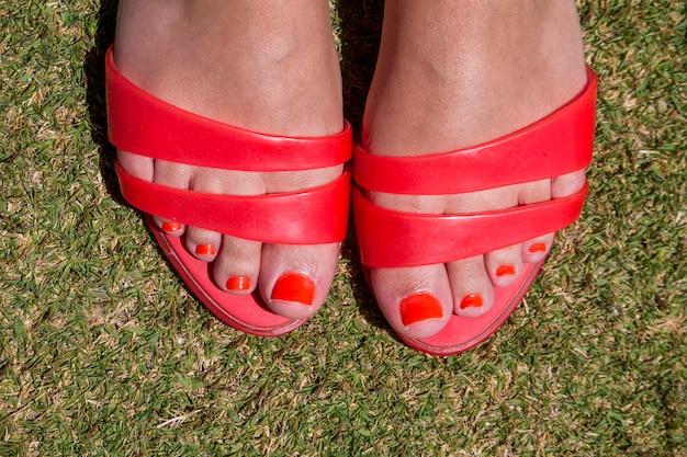 Ciérrese encima de vista de los pies de las muchachas con los clavos rojos y las sandalias rojas en hierba verde.