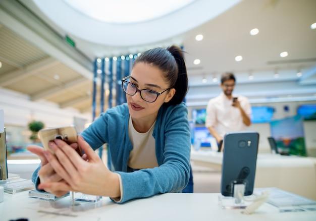 Ciérrese encima de la vista del retrato de la muchacha encantadora joven emocionada linda del estudiante con las lentes que sostienen el nuevo móvil brillante mientras que su novio prueba otro detrás de ella en una tienda de tecnología.