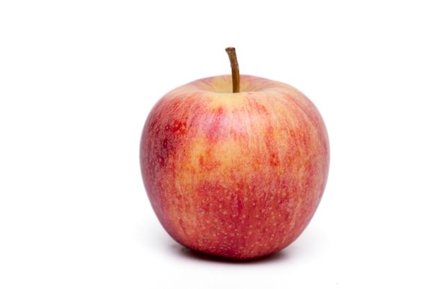 Ciérrese encima de vista de una sola manzana roja aislada en un fondo blanco.