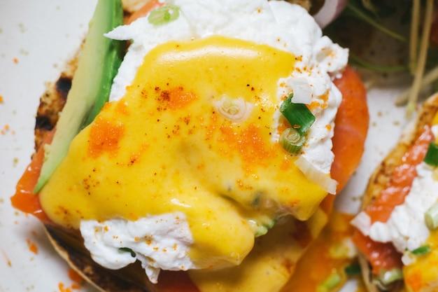 Ciérrese encima de la vista superior de los huevos benedicto con los salmones y el aguacate, servidos con la ensalada en la placa blanca.