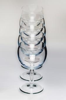 Ciérrese encima de la vista de varios vidrios vacíos alineados de vino aislados en un fondo blanco.