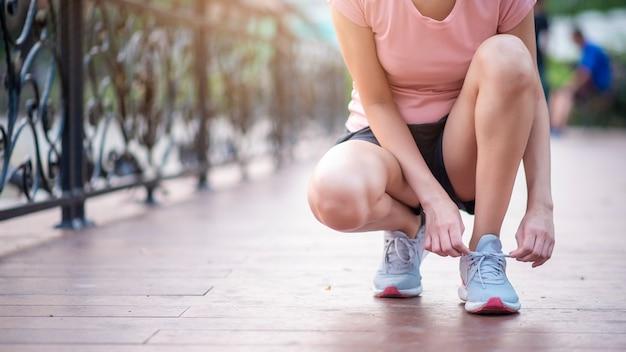 Ciérrese encima de los zapatos del lazo de la mujer en el parque