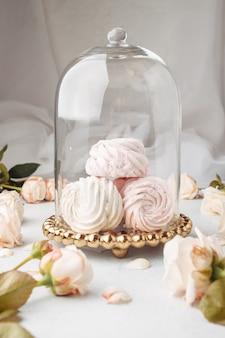 Ciérrese encima del zephyr de empaquetado de la torta en la tabla. espacio para el concepto de comida de texto. pastel en soporte y malvaviscos con elementos rosas