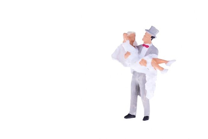Ciérrese para arriba de aislante miniatura de la novia y del novio de la boda de la boda en el fondo blanco