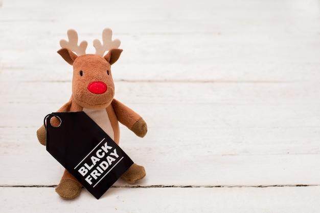 Ciervo de juguete con etiqueta de viernes negro en madera blanca con copyspace