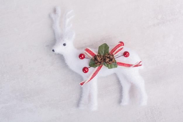 Ciervos de juguete de navidad sobre superficie blanca