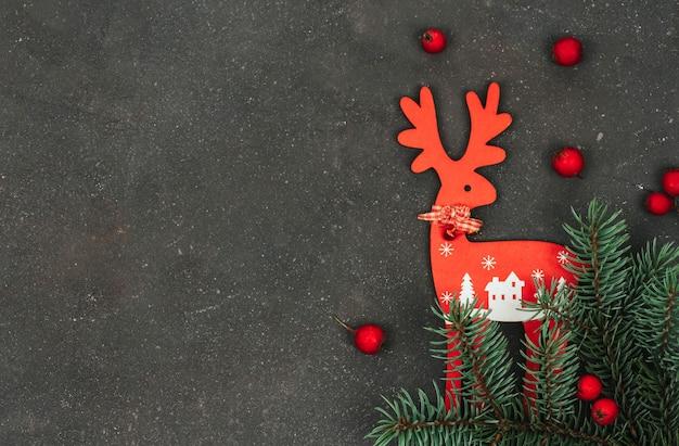 Ciervos de navidad de madera roja, ramita de abeto y pequeñas manzanas rojas