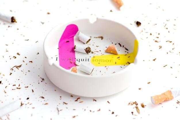 Cigarret idestroyed alrededor de cenicero blanco