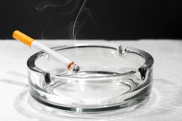 Cigarrillo en cenicero transparente sobre mesa