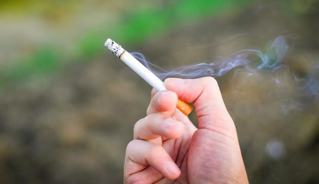 Cigarrillo en mano / humo de cigarrillo quema en mano hombre fumando en el fondo al aire libre