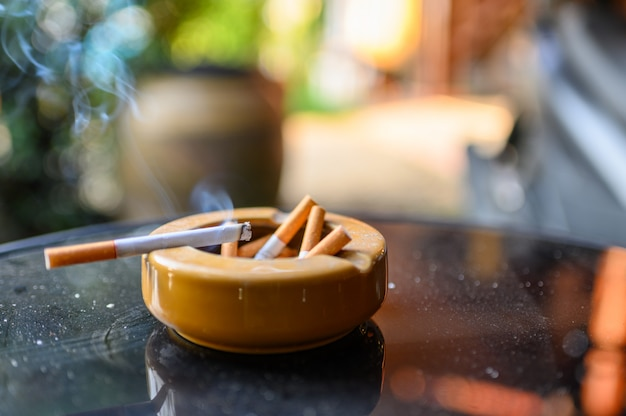 Cigarrillo que quema con fumar en el cenicero