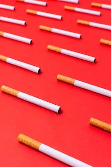 Cigarrillos de alto ángulo sobre fondo rojo.