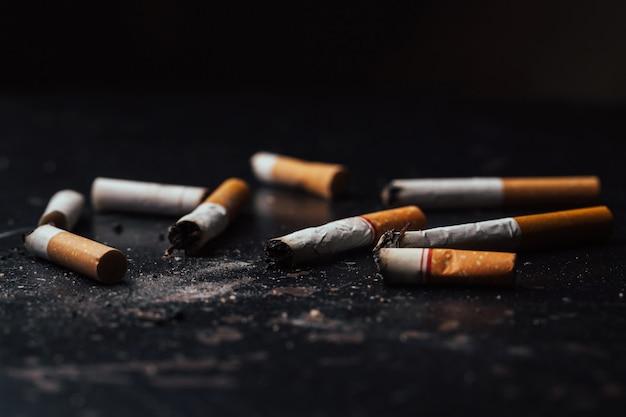 Los cigarrillos estaban quemados y humeando. el día mundial sin tabaco cae el 31 de mayo de cada año. los cigarrillos de humo fueron aplastados, en el piso negro.