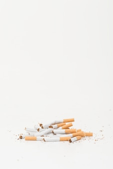 Cigarrillos rotos sobre fondo blanco con espacio de copia para escribir texto
