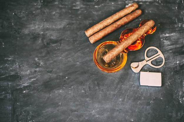 Un cigarro, un cenicero, unas tijeras de cigarrillos, un encendedor sobre una mesa de hormigón oscuro.