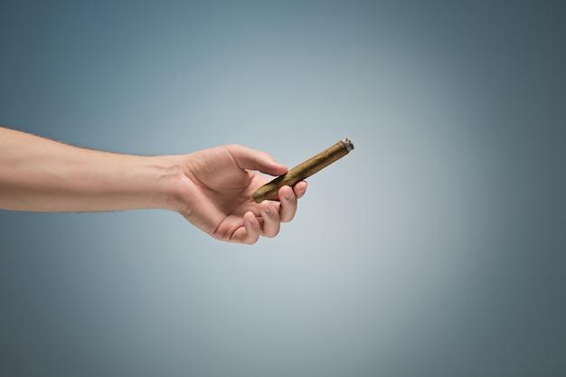 Cigarro cubano apagado en mano masculina