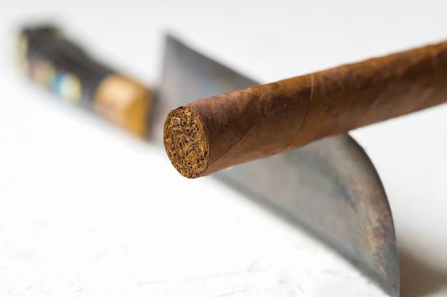 Cigarro equilibrado en el filo de un cuchillo el concepto de peligros de fumar.