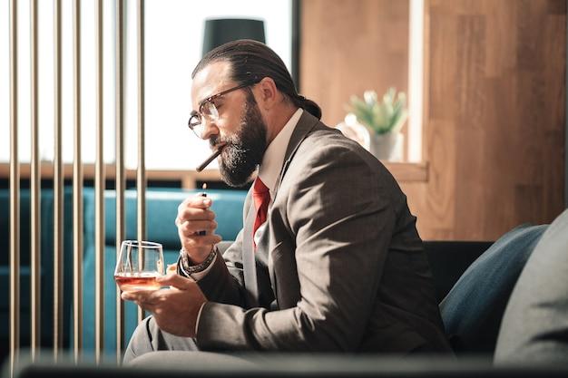 Cigarro relámpago. hombre de pelo oscuro barbudo con gafas iluminando su cigarro mientras bebe whisky
