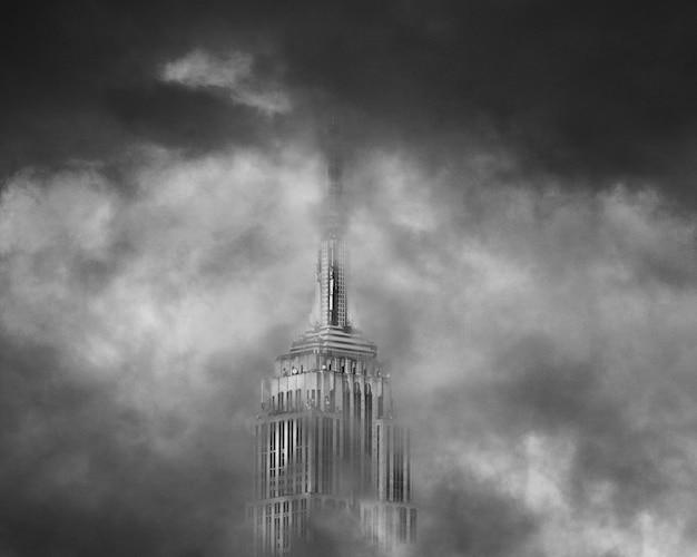 La cima de un rascacielos rodeado de nubes