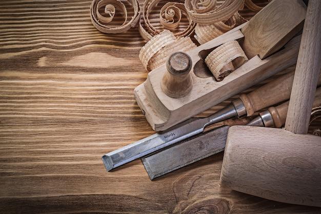 Cinceles planos cepilladora virutas rizadas terrón martillo sobre tablero de madera