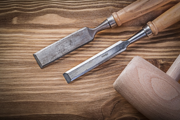 Cinceles planos mazo de madera sobre tablero de madera vintage