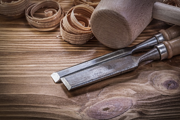 Cinceles planos virutas rizadas martillo de madera sobre tablero de madera