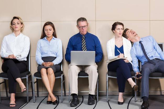Cinco aburridos hombres de negocios sentado en sala de espera