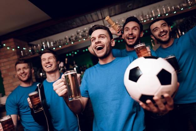 Cinco aficionados al fútbol bebiendo cerveza y celebrando en el bar.