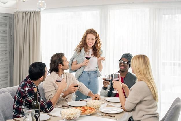 Cinco amigos interculturales felices con copas de vino tinto van a hacer un brindis de celebración mientras están sentados junto a la mesa servida