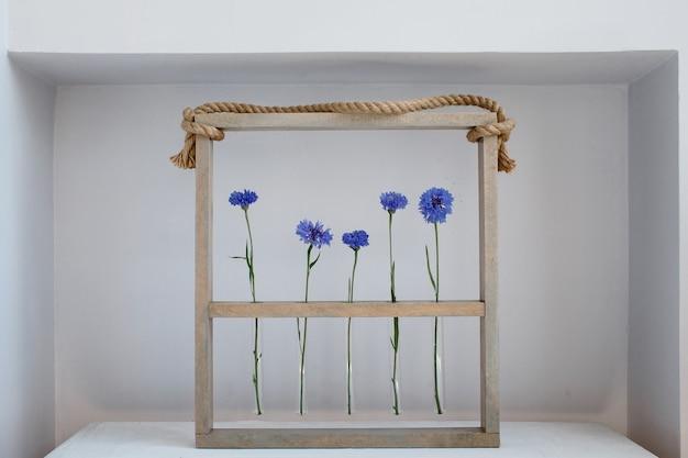 Cinco bonitos acianos azules en pequeños jarrones en un marco de madera sobre gris, simple flor de regalo y decoración en el día de san valentín