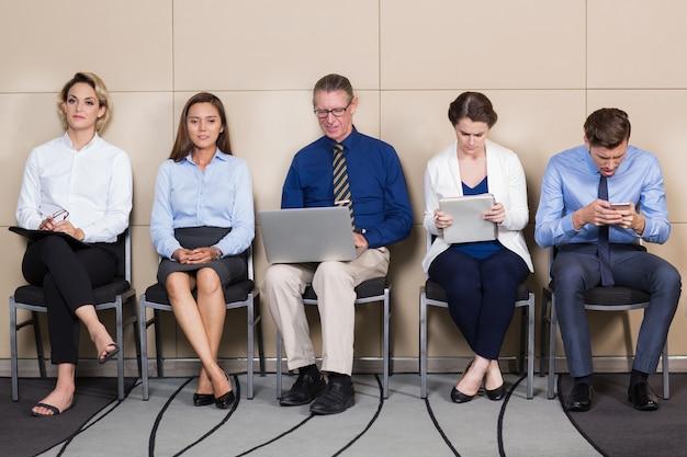 Cinco candidatos masculinos y femeninos en sala de espera
