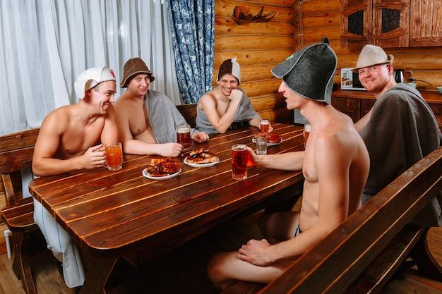 Cinco chicos se relajan en la sauna después de la sala de vapor y beben cerveza.
