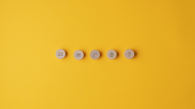 Cinco círculos cortados de madera con iconos de contacto e información colocados en una fila