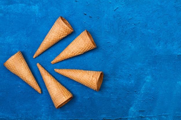 Cinco conos de oblea sobre un fondo azul con textura en una vista superior
