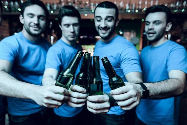 Cinco fanáticos del deporte bebiendo cerveza y celebrando.