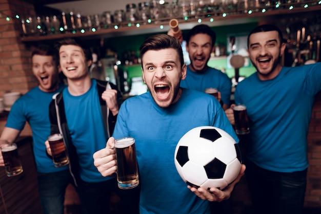 Cinco fanáticos del fútbol bebiendo cerveza celebrando en el bar.
