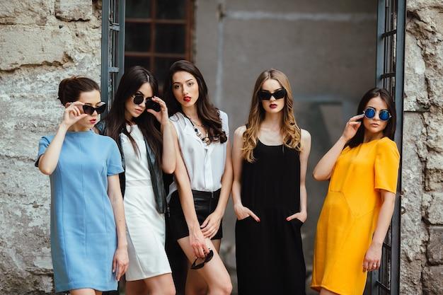 Cinco hermosas chicas jóvenes posando en contra de un edificio abandonado