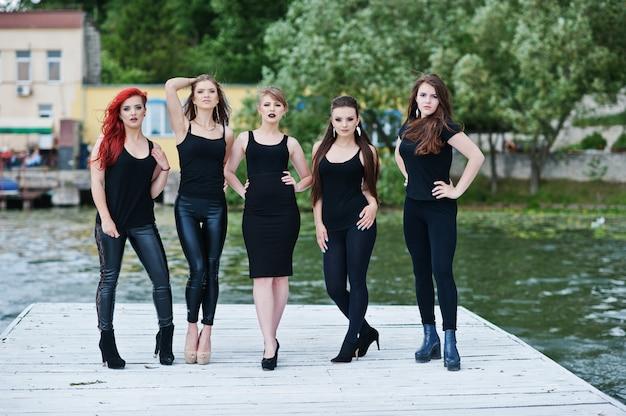 Cinco hermosas modelos de chicas jóvenes y sexy en vestido negro ajustado posando en el muelle