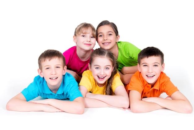 Cinco hermosos niños sonrientes tendidos en el suelo con camisetas de colores brillantes, aislados en blanco.