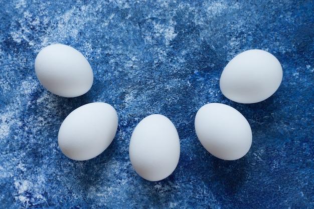 Cinco huevos blancos yacen sobre un fondo azul elevado en forma de semicírculo.
