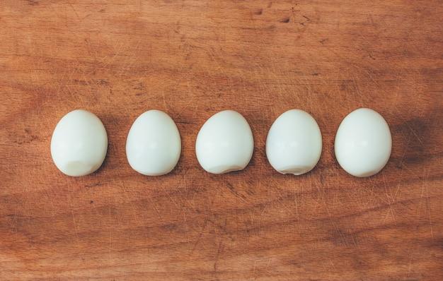 Cinco huevos cocidos pelados en una fila sobre una vieja tabla de cortar. vista desde arriba, primer plano, foto tonificante