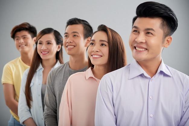 Cinco jóvenes de pie en fila mirando hacia los lados