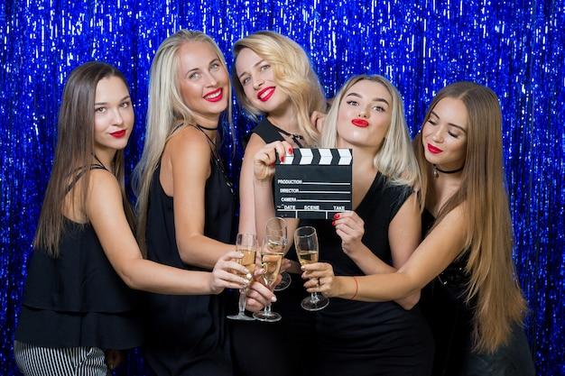Cinco mujeres encantadoras con lápiz labial rojo en sus labios con vestidos negros con copas de champán en un azul brillante