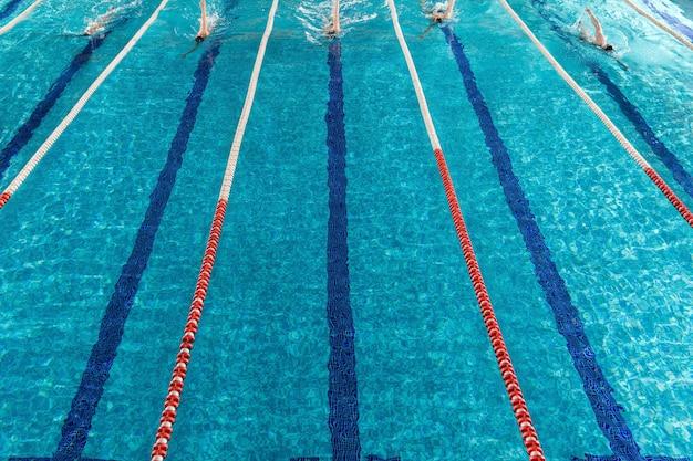 Cinco nadadores varones corriendo uno contra el otro