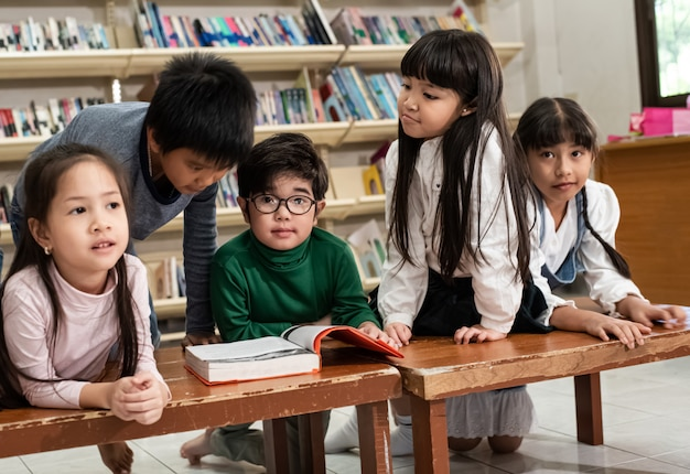 Cinco niños acostados en un escritorio de madera, hablando y leyendo libros, haciendo actividades juntos, en la escuela, con la luz borrosa alrededor