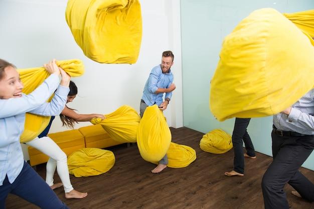 Cinco personas descuidadas luchando con almohadas