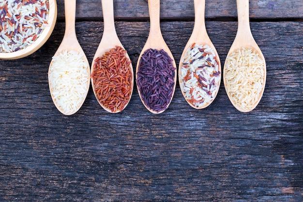 Cinco tipos de arroz orgánico sobre suelo de madera.