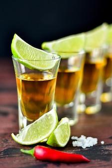 Cinco vasos de alcohol con bocadillos de lima y pistacho, sal y ají para decoración. chupitos de tequila, vodka, whisky, ron