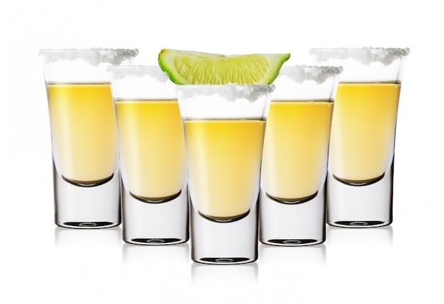 Cinco vasos de tequila dorado con sal y lima