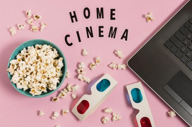 Cine en casa con computadora portátil y palomitas de maíz